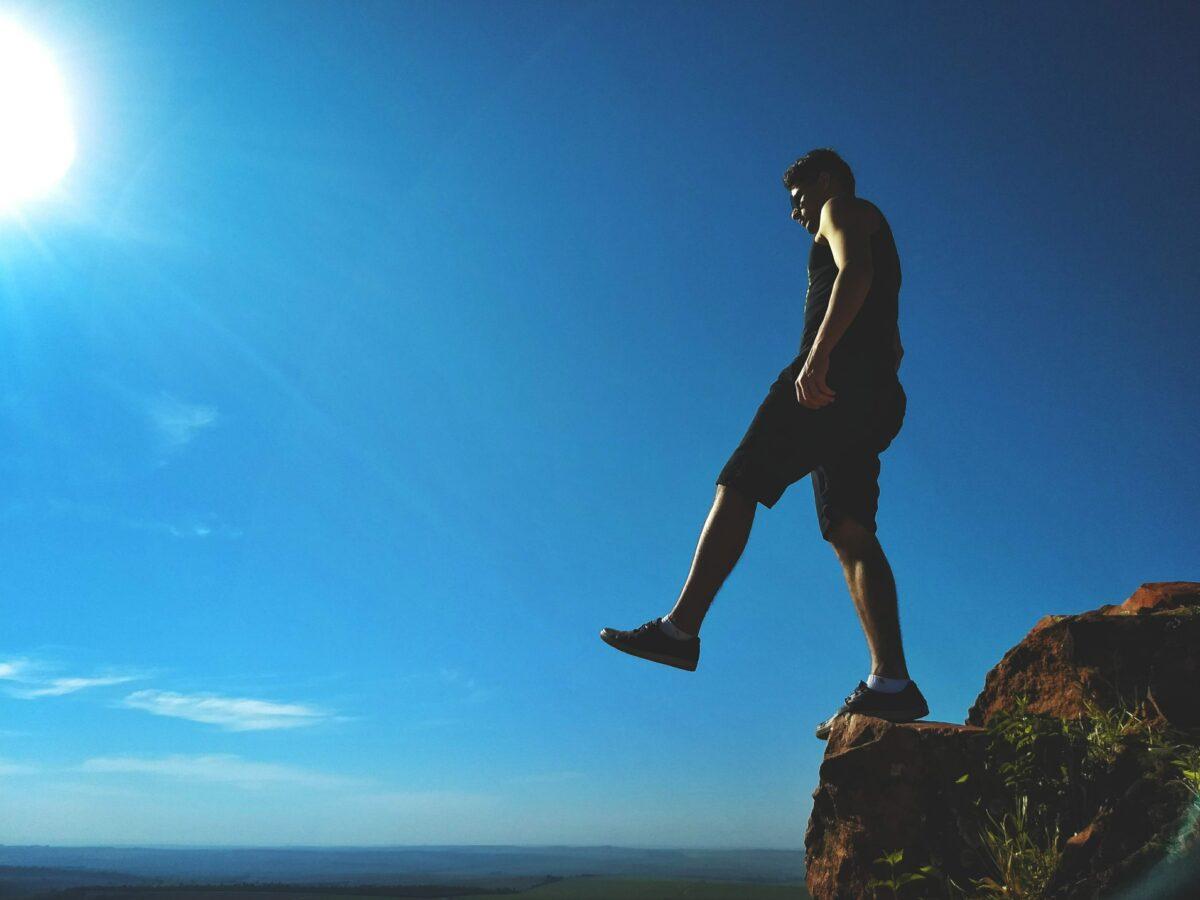 A man stepping off a cliff